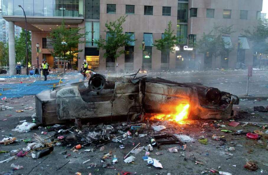 A burnt out car lies upside down in the street following the Vancouver Canucks being defeated by the