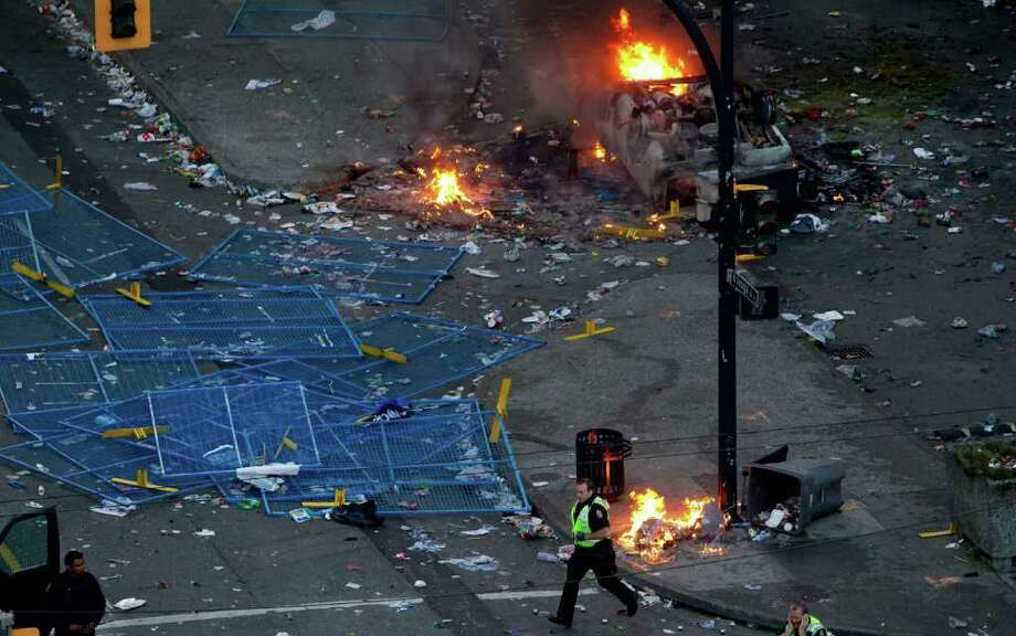 A police officer walks amid debris following the Vancouver Canucks being defeated by the Boston Bruins in the NHL Stanley Cup Final in Vancouver, British Columbia, Wednesday, June 15, 2011. Angry, drunken revelers ran wild Wednesday night after the Vancouver Canucks' 4-0 loss to Boston in Game 7 of the Stanley Cup finals, setting cars and garbage cans ablaze, smashing windows, showering giant TV screens with beer bottles and dancing atop overturned vehicles. Photo: AP