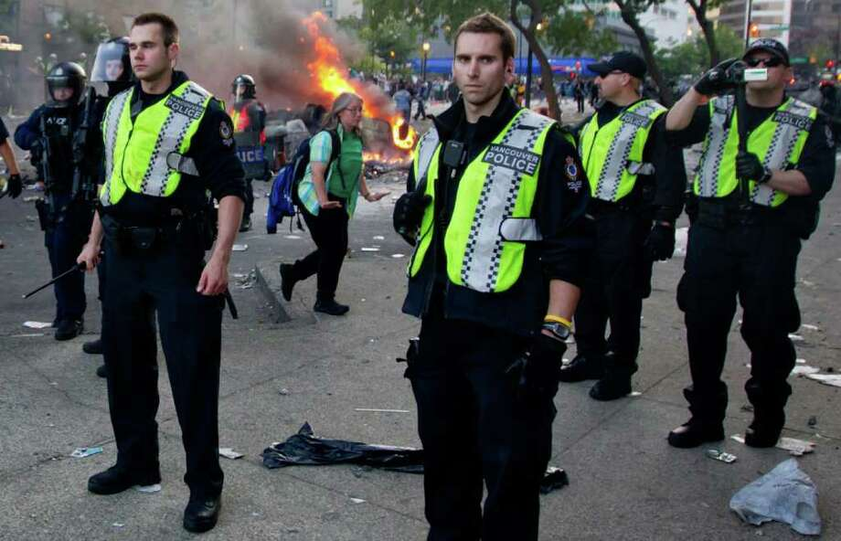 Police officers stand together after rioters burned police cars following the Vancouver Canucks being defeated by the Boston Bruins in the NHL Stanley Cup Final in Vancouver, British Columbia, Wednesday, June 15, 2011. Angry, drunken revelers ran wild Wednesday night after the Vancouver Canucks' 4-0 loss to Boston in Game 7 of the Stanley Cup finals, setting cars and garbage cans ablaze, smashing windows, showering giant TV screens with beer bottles and dancing atop overturned vehicles. Photo: AP