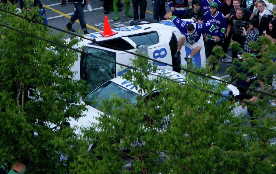 A Vancouver Canucks fan jumps from a police car that was overturned by rioters following the Vancouv