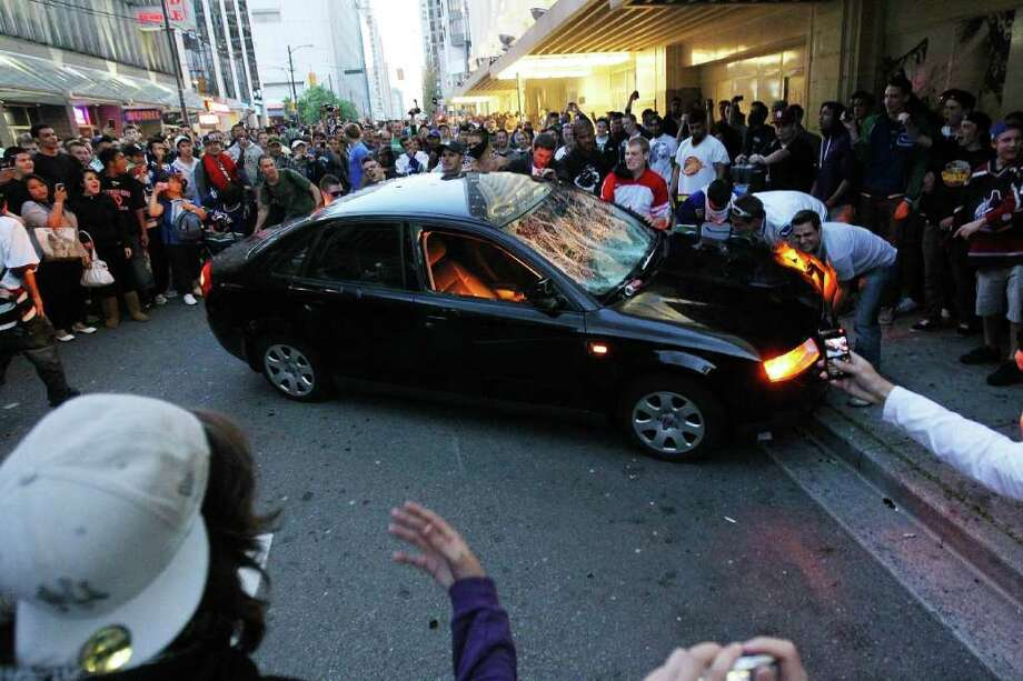 Rioters try to flip a car on June 15, 2011 in Vancouver, Canada. Vancouver broke out in riots after their hockey team the Vancouver Canucks lost in Game Seven of the Stanley Cup Finals. Photo: Bruce Bennett, Getty Images / 2011 Getty Images