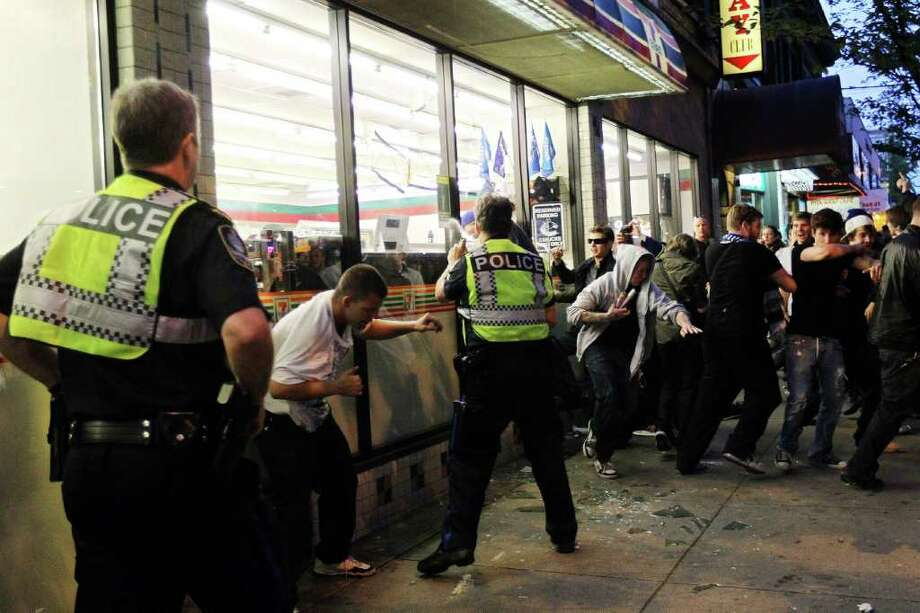 Police officers pepper spray a group of rioters trying to break into a 7-11 on June 15, 2011 in Vancouver, Canada. Vancouver broke out in riots after their hockey team the Vancouver Canucks lost in Game Seven of the Stanley Cup Finals. Photo: Bruce Bennett, Getty Images / 2011 Getty Images