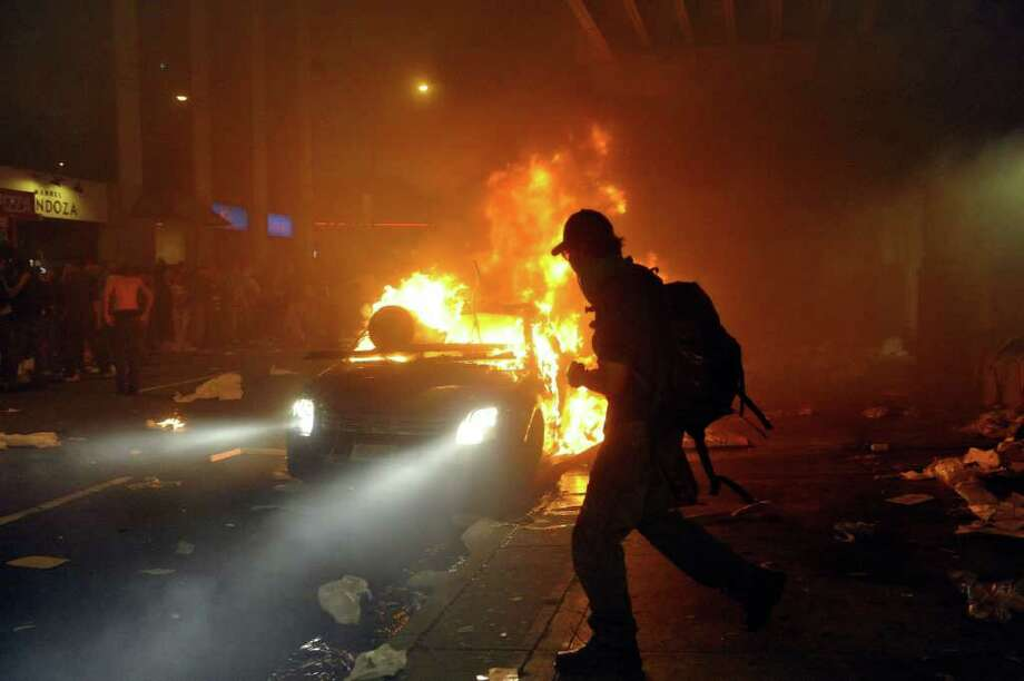 A person walks in front of a burning vehicle on June 15, 2011 in Vancouver, Canada. Vancouver broke out in riots after their hockey team the Vancouver Canucks lost in Game Seven of the Stanley Cup Finals. Photo: Rich Lam, Getty Images / 2011 Getty Images