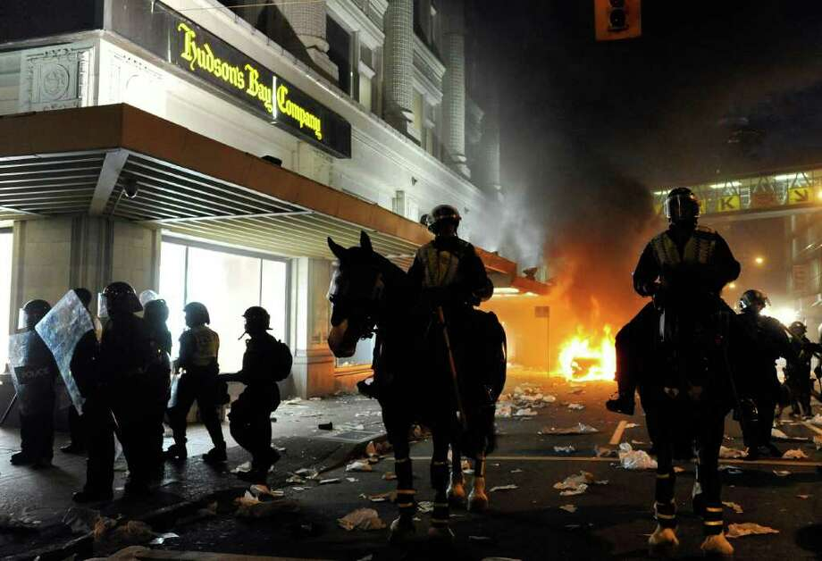 Police on horseback ride through the street past a fire on June 15, 2011 in Vancouver, Canada. Vancouver broke out in riots after their hockey team the Vancouver Canucks lost in Game Seven of the Stanley Cup Finals. Photo: Rich Lam, Getty Images / 2011 Getty Images