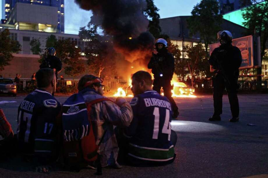 Riot police stand in front of two burning police cars as people look on June 15, 2011 in Vancouver, Canada. Vancouver broke out in riots after their hockey team the Vancouver Canucks lost in Game Seven of the Stanley Cup Finals. Photo: Elsa, Getty Images / 2011 Getty Images