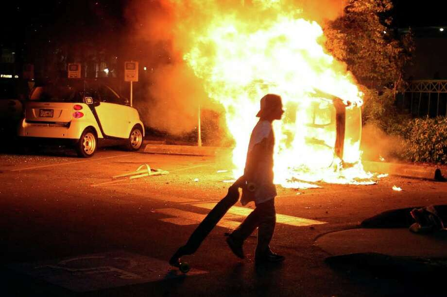 A person walks in front of a burning vehicle on June 15, 2011 in Vancouver, Canada. Vancouver broke out in riots after their hockey team the Vancouver Canucks lost in Game Seven of the Stanley Cup Finals. Photo: Elsa, Getty Images / 2011 Getty Images