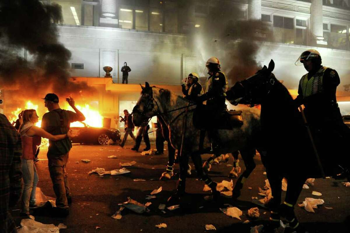 Police on horseback ride through the street past a fire on June 15, 2011 in Vancouver, Canada. Vancouver broke out in riots after their hockey team the Vancouver Canucks lost in Game Seven of the Stanley Cup Finals.
