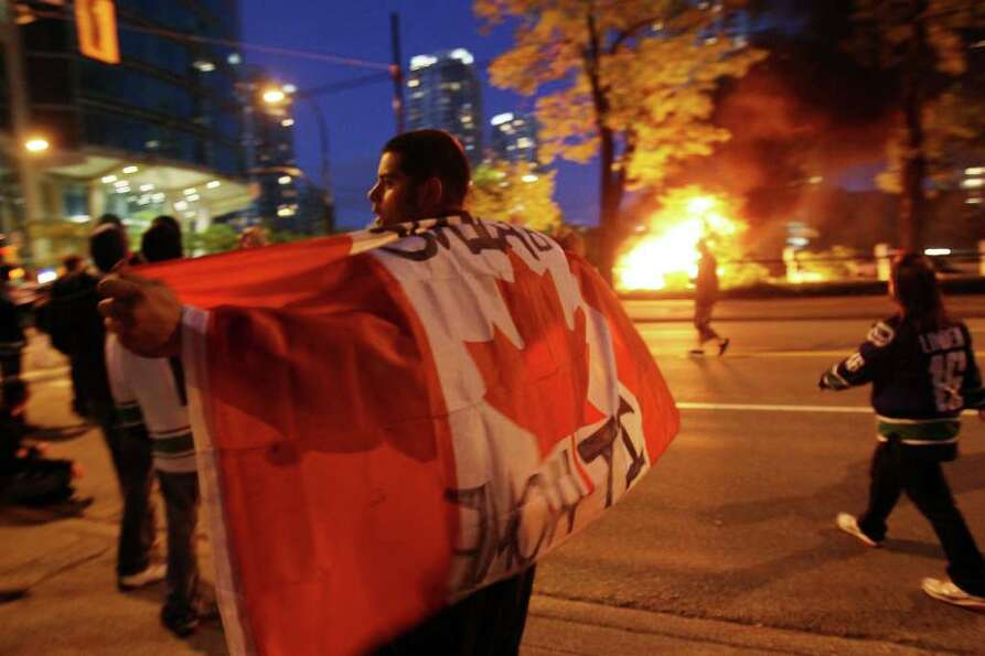A person with a Candanian flag walks in front of a burning vehicle on June 15, 2011 in Vancouver, Ca
