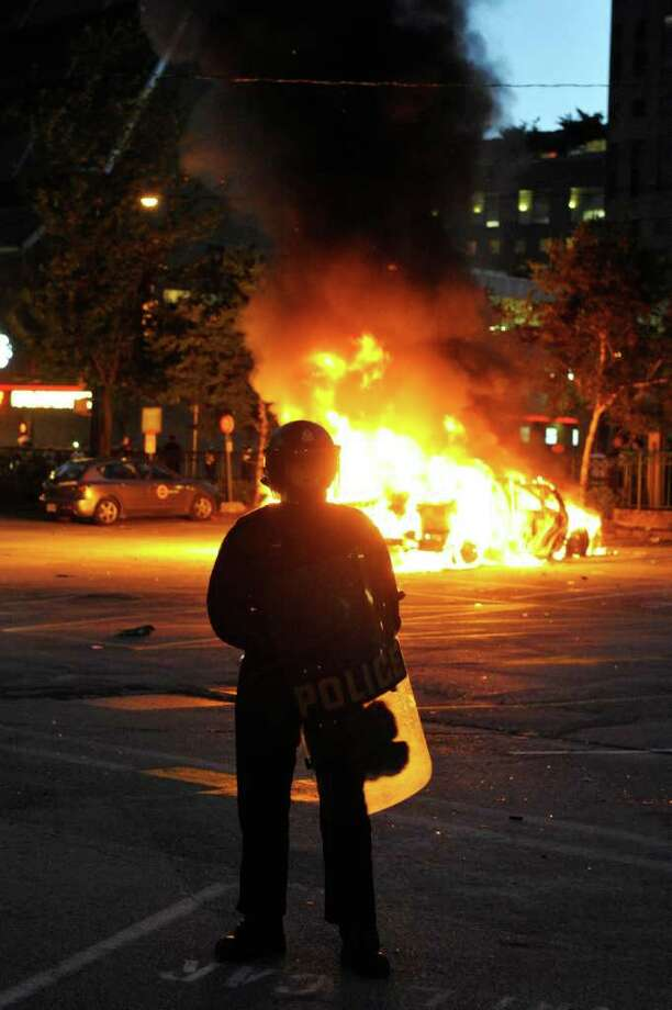 Riot police stand in front of a burning vehicle on June 15, 2011 in Vancouver, Canada. Vancouver broke out in riots after their hockey team the Vancouver Canucks lost in Game Seven of the Stanley Cup Finals. Photo: Rich Lam, Getty Images / 2011 Getty Images