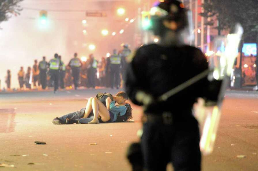 Riot police walk in the street as a couple kiss on June 15, 2011 in Vancouver, Canada. Vancouver bro