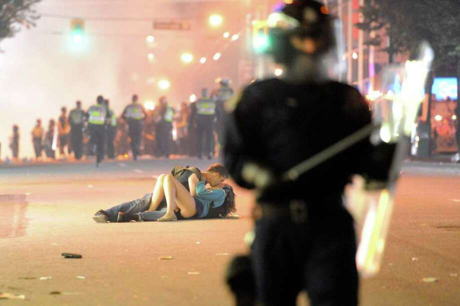 Riot police walk in the street as a couple kiss on June 15, 2011 in Vancouver, Canada. Vancouver broke out in riots after their hockey team the Vancouver Canucks lost in Game Seven of the Stanley Cup Finals. Photo: Rich Lam, Getty Images / 2011 Getty Images