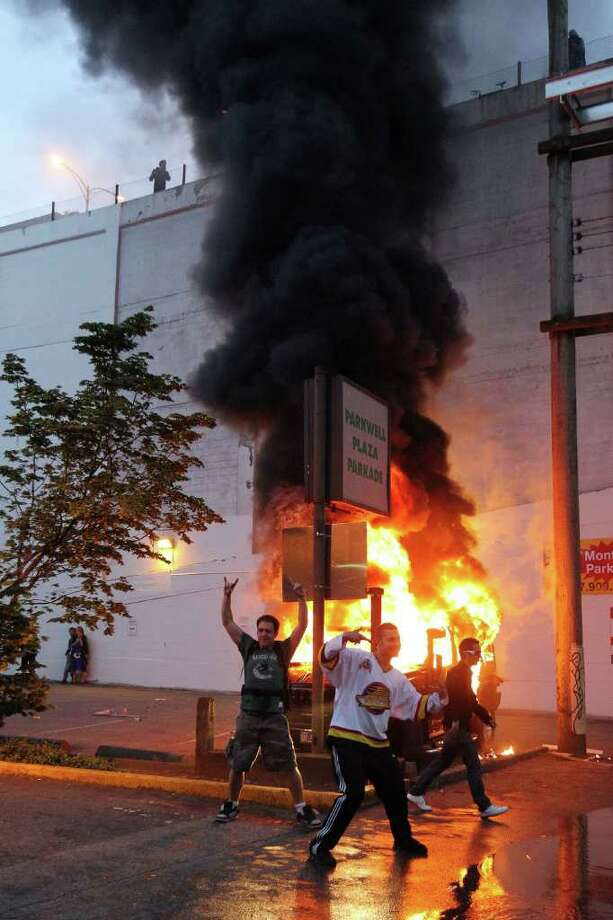 People pose in front of a burning vehicle on June 15, 2011 in Vancouver, Canada. Vancouver broke out in riots after their hockey team the Vancouver Canucks lost in Game Seven of the Stanley Cup Finals. Photo: Bruce Bennett, Getty Images / 2011 Getty Images