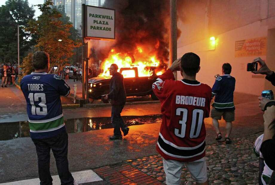 People take pictures of a burning vehicle on June 15, 2011 in Vancouver, Canada. Vancouver broke out in riots after their hockey team the Vancouver Canucks lost in Game Seven of the Stanley Cup Finals. Photo: Bruce Bennett, Getty Images / 2011 Getty Images