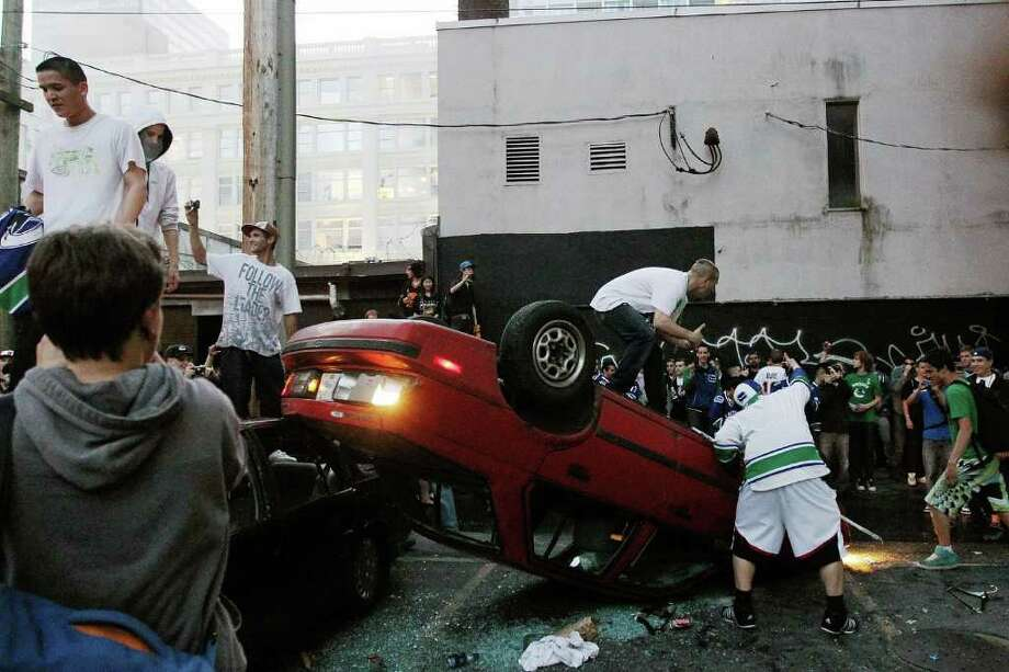 People flip a vehicle on June 15, 2011 in Vancouver, Canada. Vancouver broke out in riots after their hockey team the Vancouver Canucks lost in Game Seven of the Stanley Cup Finals. Photo: Bruce Bennett, Getty Images / 2011 Getty Images