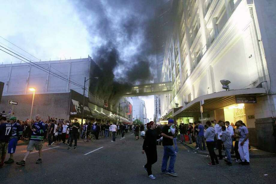 People walk in the street as smoke billows out of a building on June 15, 2011 in Vancouver, Canada. Vancouver broke out in riots after their hockey team the Vancouver Canucks lost in Game Seven of the Stanley Cup Finals. Photo: Bruce Bennett, Getty Images / 2011 Getty Images