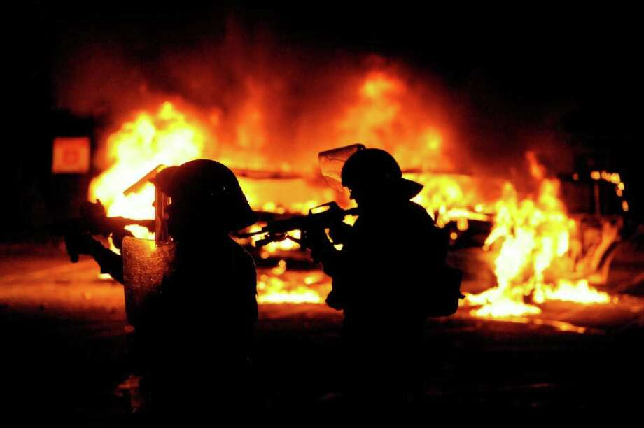 Riot police walk in front of a burning vehicle on June 15, 2011 in Vancouver, Canada. Vancouver broke out in riots after their hockey team the Vancouver Canucks lost in Game Seven of the Stanley Cup Finals. Photo: Rich Lam, Getty Images / 2011 Getty Images