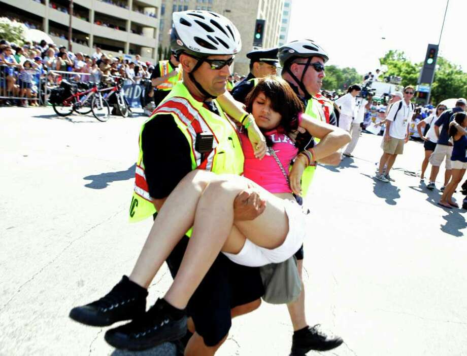 Dallas police carry a young woman who passed out while waiting for the start of the victory parade for the Dallas Mavericks in downtown Dallas, Thursday, June 16, 2011. The Mavericks beat the Miami Heat to win the NBA championship. Photo: AP