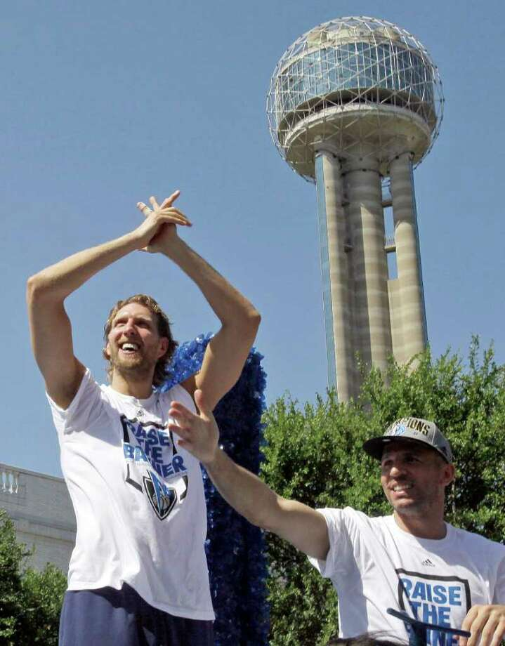 Dallas Mavericks Dirk Nowitzki, left, of Germany, and teammate Jason Kidd ride past Reunion Tower during the team's victory parade in downtown Dallas, Thursday, June 16, 2011. The Mavericks beat the Miami Heat to win the NBA championship. Photo: AP