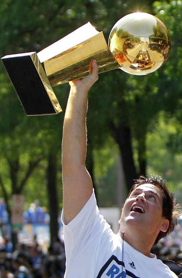 Dallas Mavericks owner Mark Cuban holds up the NBA Championship basketball trophy during the team's victory parade in downtown Dallas, Thursday, June 16, 2011. The Mavericks beat the Miami Heat to win the NBA championship. Photo: AP