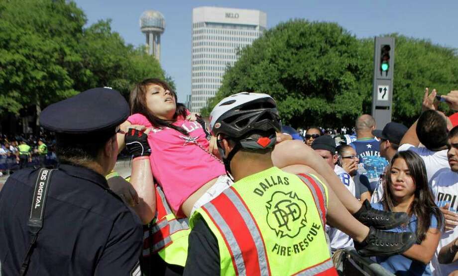 Dallas police carry a young woman that passed out while waiting for the start of the victory parade for the Dallas Mavericks in downtown Dallas, Thursday, June 16, 2011. The Mavericks beat the Miami Heat to win the NBA championship. Photo: AP