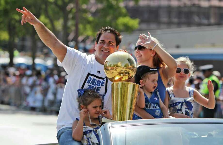 Dallas Mavericks owner Mark Cuban rides with the NBA Championship basketball trophy and his family wife Tiffany, holding son Jake, and daughters Alexis Sofia, right, and Alyssa, during the team's victory parade in downtown Dallas, Thursday, June 16, 2011. The Mavericks beat the Miami Heat to win the NBA championship. Photo: AP