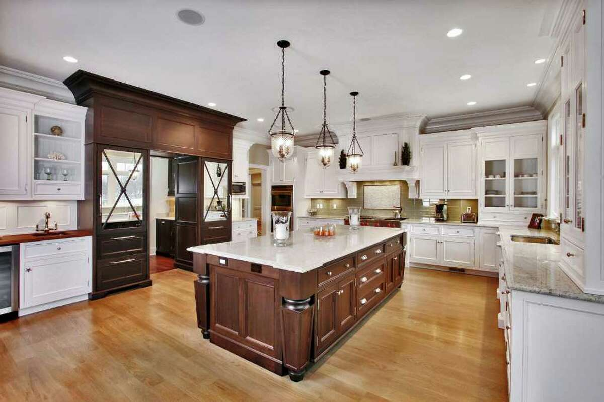 The kitchen features polished granite counters, a large center island, an opera glass tile backsplash and top-of-the-line appliances, including Wolf double, wall-mounted ovens, a six-burner Wolf range top and a Sub-Zero refrigerator.