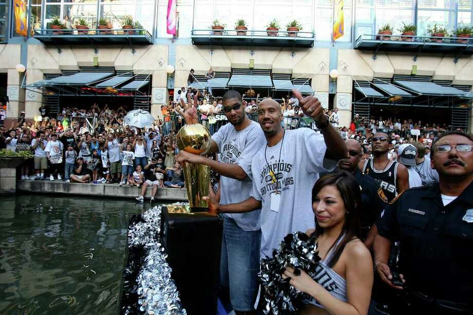 FOR METRO - Spurs' forward Tim Duncan (21) and Bruce Bowen wave to the crowds during the victory parade Sunday June 17, 2007, at the River Center Lagoon (EDWARD A. ORNELAS/STAFF) Photo: EDWARD A. ORNELAS, SAN ANTONIO EXPRESS-NEWS / SAN ANTONIO EXPRESS-NEWS