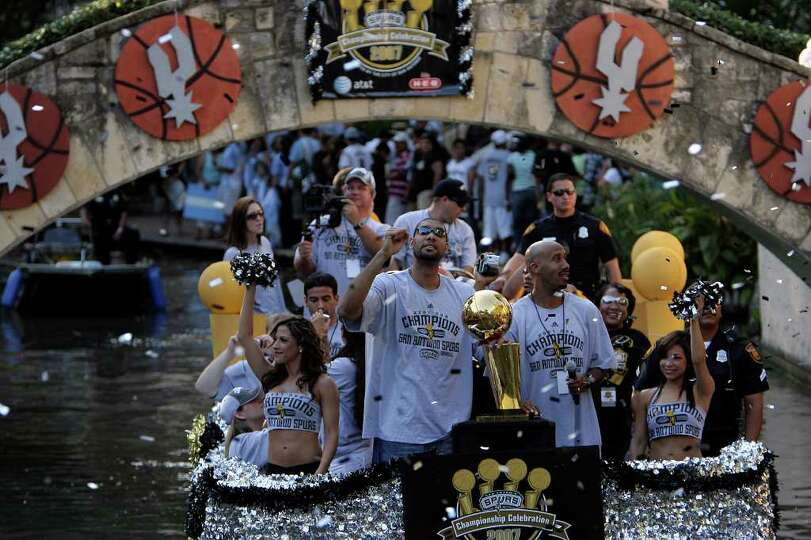 San Antonio Spurs Tim Duncan, center left, checks out the confetti along with Bruce Bowen, as they a