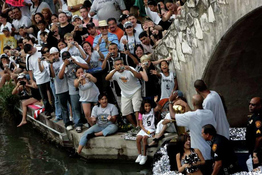 METRO - Fans cheer as Bruce Bowen, left, and Tim Duncan, right, round the bend near the Commerce Street bridge during the Spurs NBA Championship river parade on Sunday, June 17, 2007. Lisa Krantz/STAFF Photo: LISA KRANTZ, SAN ANTONIO EXPRESS-NEWS / SAN ANTONIO EXPRESS-NEWS