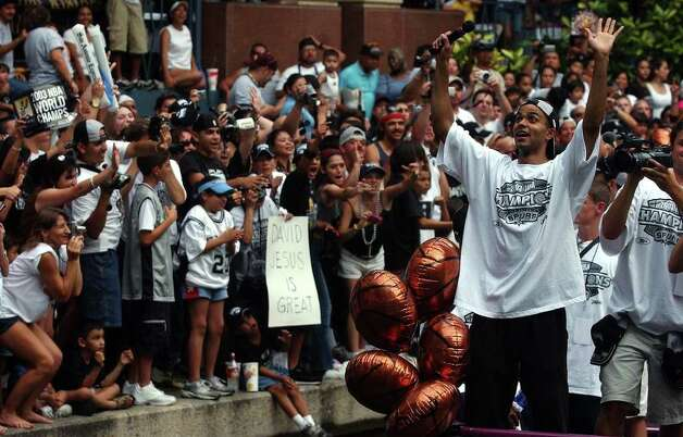 Tony Parker (right) waves to the crowd in the RiverCenter Mall laguna during the Spurs river parade along the RiverWalk in San Antonio on Wednesday, June 18, 2003. (Kin Man Hui/Staff) Photo: KIN MAN HUI, SAN ANTONIO EXPRESS-NEWS / SAN ANTONIO EXPRESS-NEWS
