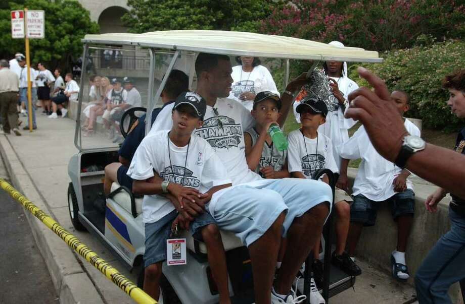 METRO -- David Robinson and his kids hitch a ride at the end of Parade Route Spurs Championship parade at Municipal Auditorium Wednesday June 18, 2003.  (Robert McLeroy/Staff) Photo: ROBERT MCLEROY, SAN ANTONIO EXPRESS-NEWS / SAN ANTONIO EXPRESS-NEWS