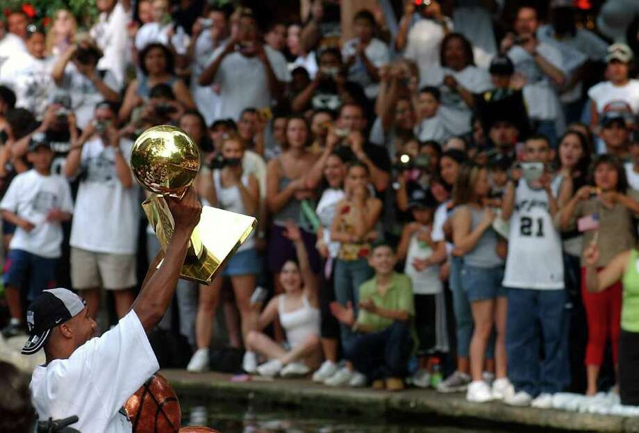 METRO   ---   The Spurs' Bruce Bowen holds up the 1999 championship trophy for the crowd Wednesday evening June 18, 2003 during the SBC 2003 Spurs Championship Celebration river parade. (WILLIAM LUTHER/STAFF) Photo: WILLIAM LUTHER, SAN ANTONIO EXPRESS-NEWS / SAN ANTONIO EXPRESS-NEWS