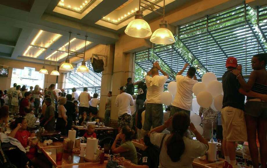 METRO - Spurs fans stand on the tables at Rivercenter Mall restaraunts to cheer the team as they move through the lagoon during the Spurs Championship parade Wednesday, June 18, 2003. BAHRAM MARK SOBHANI/STAFF Photo: BAHRAM MARK SOBHANI, SAN ANTONIO EXPRESS-NEWS / SAN ANTONIO EXPRESS-NEWS