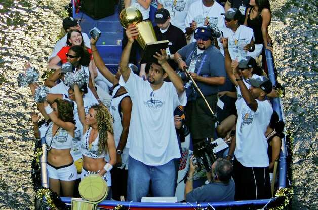 METRO - Tim Duncan hoists a Larry O'Brien trophy as he rides with teammate Bruce Bowen during the Spurs championship parade Saturday, June 25, 2005 on the San Antonio River. BAHRAM MARK SOBHANI/STAFF Photo: BAHRAM MARK SOBHANI, SAN ANTONIO EXPRESS NEWS / SAN ANTONIO EXPRESS NEWS