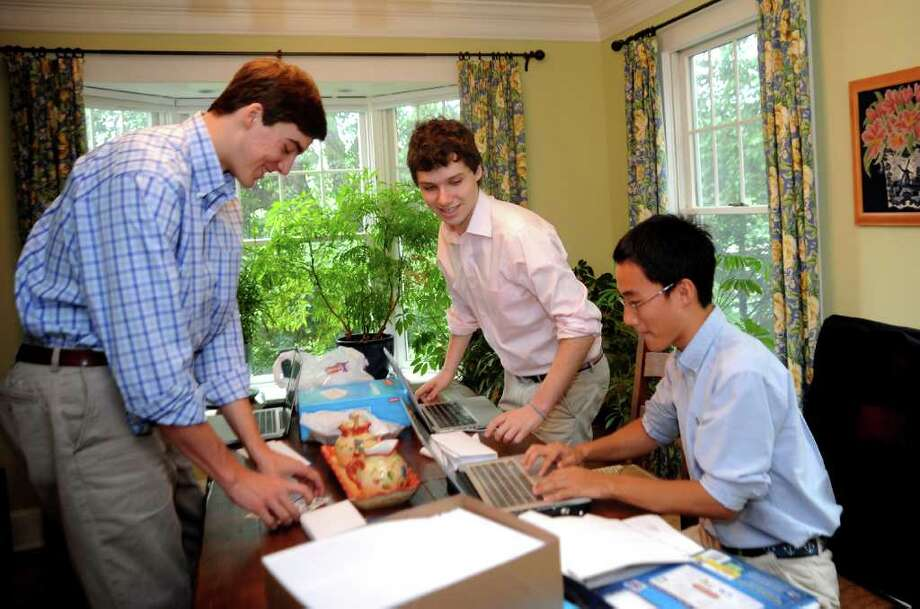 Luke Crihfield, 20, of Greenwich, a student at Georgetown University; Andrew Beinstein, 18, of Riverside, a student at University of Chicago; and Jae Young Lee, of Greenwich, a student at Princeton University, work together mailing information about their new SAT tutoring service in the Beinstein home on Thursday, June 16, 2011. The three college students have opened a branch of the Ivy Insiders' SAT tutoring service in town. Photo: Helen Neafsey / Greenwich Time
