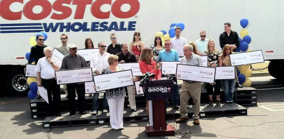 Twenty Costco employees receive oversized checks in the amount of $201 million during an awards ceremony at the Costco store in Melville, N.Y., Thursday, June 16, 2011, for winning the June 1 Powerball lottery. The group, who chipped in $5 a week  each to pool their money for lottery tickets, have only been playing Powerball together for about a month. They will split $70.2 million after taxes. (AP Photo/Newsday, Ed Betz) NYC LOCALS OUT; MAGS OUT; NO SALES Photo: Ed Betz