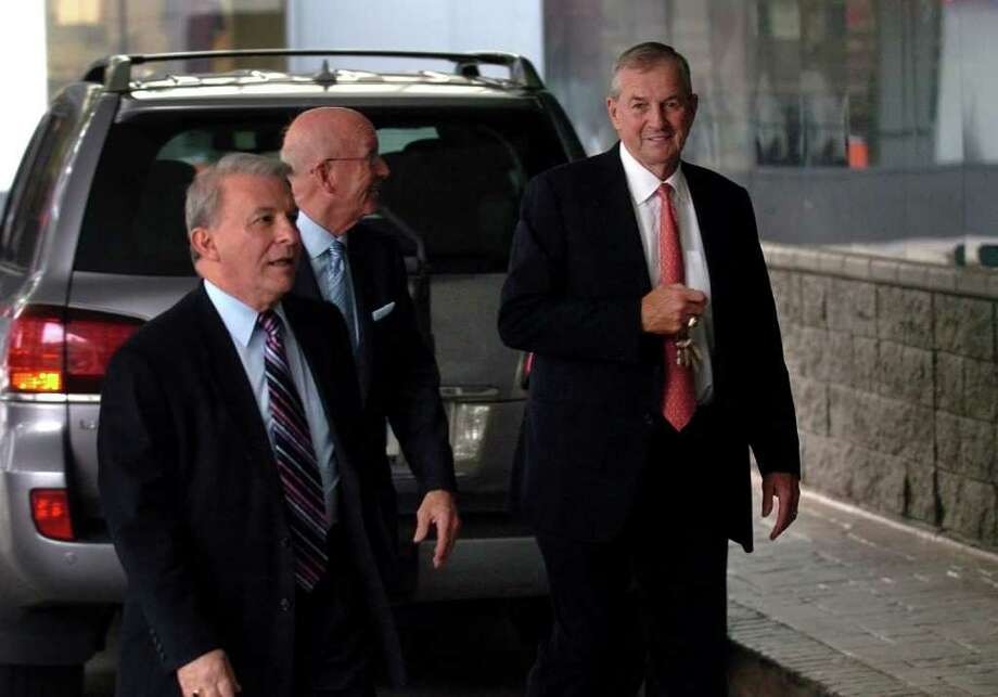 UConn Coach Jim Calhoun, right, arrives at the St. Vincent's Swim Across the Sound 8th Annual Prostate Cancer Institue Celebrity Dinner which was held at the Holiday Inn in downtwon Bridgeport, Conn. on Thursday June 16, 2011. Accompanying Calhoun is Mike Bisciglia, VP of St. Vincent's Medical Center Foundation, at left, and Bill Mitchell, President of Mitchells Westport. Photo: Christian Abraham / Connecticut Post