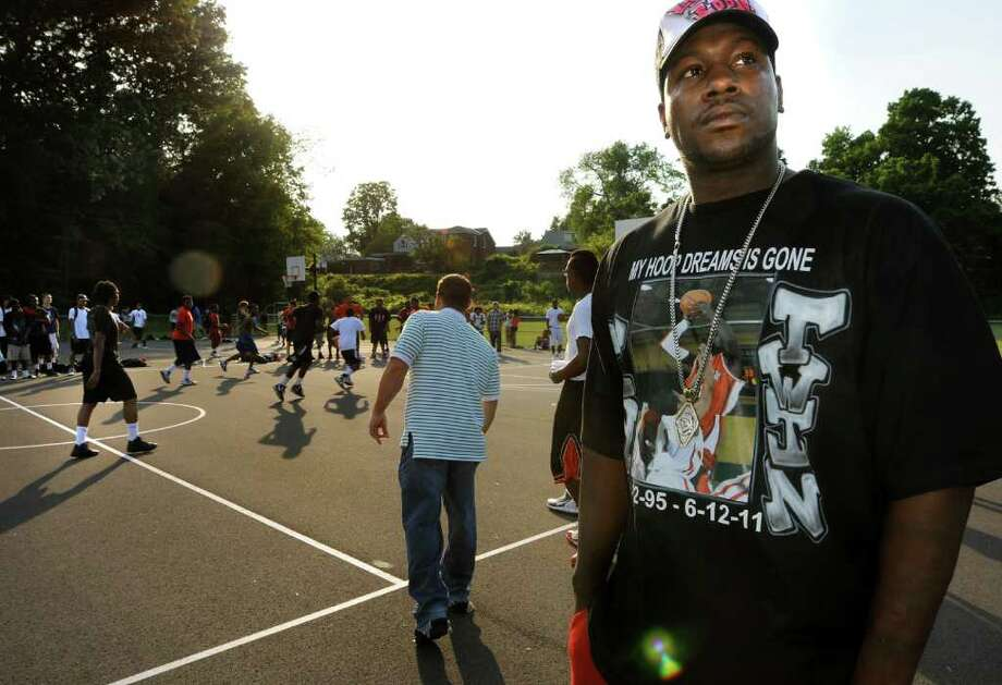Eddie Stanley Sr., right, wears a shirt in honor of his slain son, Eddie, during a basketball game to help the family with funeral expenses on Thursday, June 16, 2011, at Central Park in Schenectady, N.Y. (Cindy Schultz / Times Union) Photo: Cindy Schultz