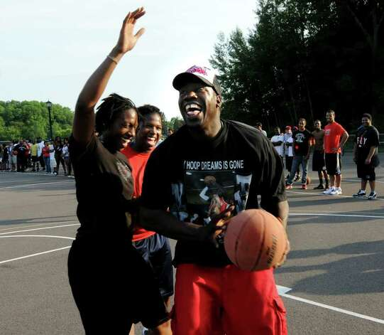 Eddie Stanley Sr., right, has a moment of fun when he steps in to play basketball with friends of his slain son, Eddie, during a game to help raise money for funeral expenses on Thursday, June 16, 2011, at Central Park in Schenectady, N.Y. (Cindy Schultz / Times Union) Photo: Cindy Schultz