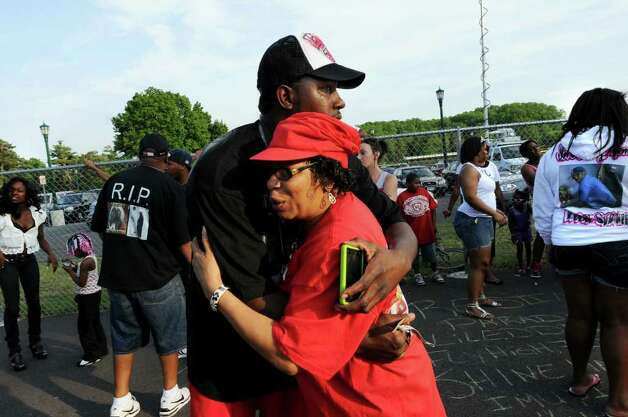 Eddie Stanley Sr., center, hugs his aunt Pamela Gentry at a basketball game that friends of his slain son, Eddie, organized to help raise money for funeral expenses on Thursday, June 16, 2011, at Central Park in Schenectady, N.Y. (Cindy Schultz / Times Union) Photo: Cindy Schultz