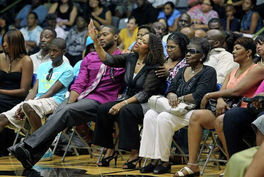 Diana Mitchell raises her hand as her son MIke Mitchell, Jr. comforts her during the memorial service for Spurs great Mike Mitchell at the Antioch Sports Center on June 16, 2011. The widow was responding to a chant called