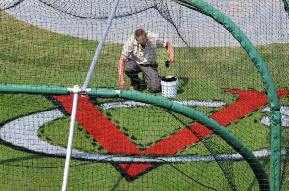 Valley Cats grounds crew Andrew Christie paints the teams emblem behind home plate at Joe Bruno Stadium in Troy, N.Y. Thursday June 16, 2011.  (Lori Van Buren / Times Union) Photo: Lori Van Buren
