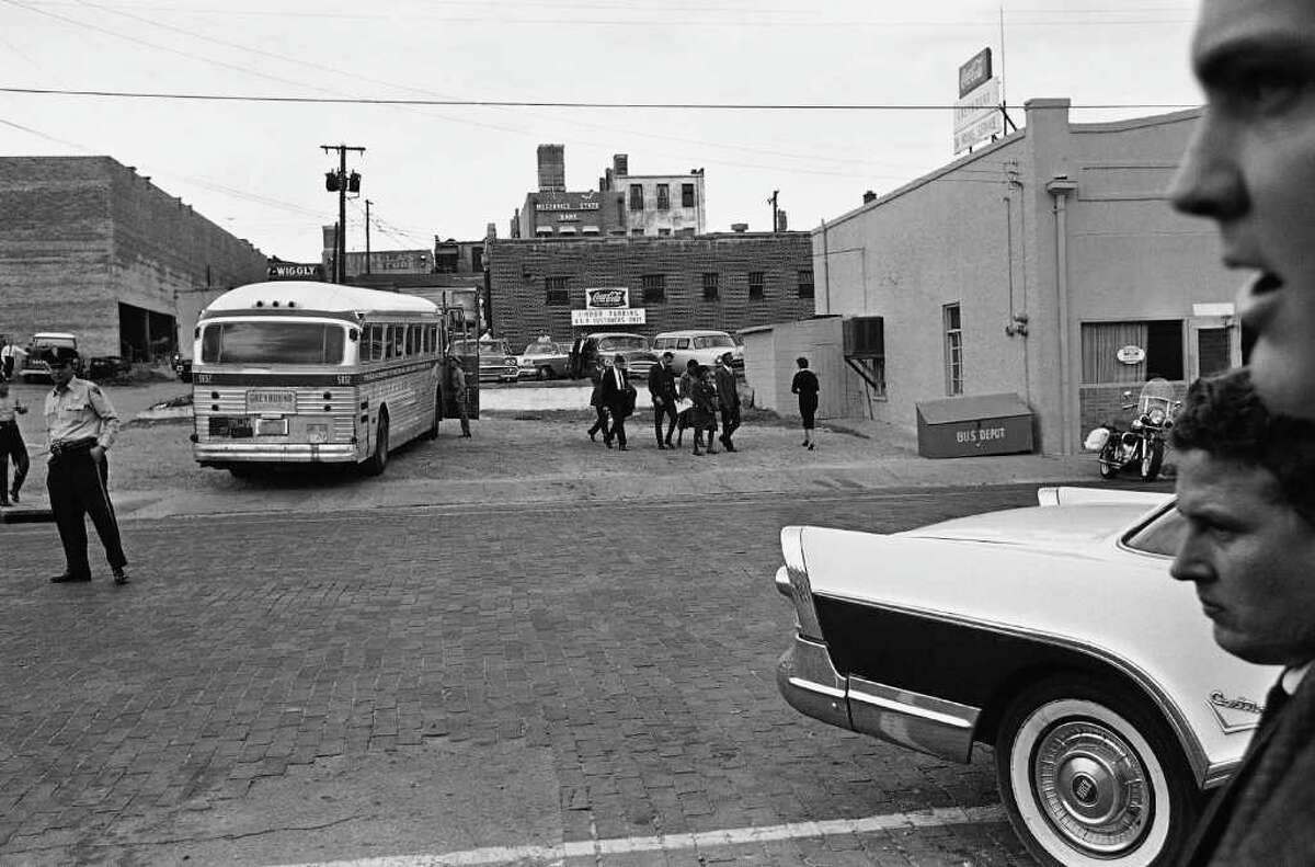 """""""Freedom Riders"""" are shown as they walked away from the bus they arrived on in McComb, Dec. 1, 1961. They walked to a car and were escorted away by police. (AP Photo/Fred Kaufman)"""