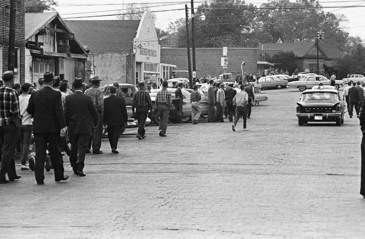 """Police escort """"Freedom Riders"""" from the bus station in McComb, Dec. 1, 1961, after they arrived on a bus with no incident. The crowd followed to the city hall where police took newsmen inside for protection. (AP Photo/Fred Kaufman)"""