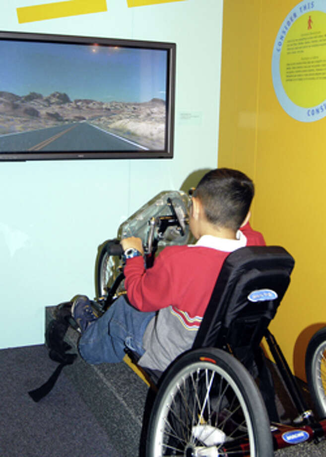In a the new interactive exhibit at Stepping Stones that promotes disability awareness, visitors can try a hand-pedaled bike and go on a virtual tour. Photo: Contributed Photo / Norwalk Citizen
