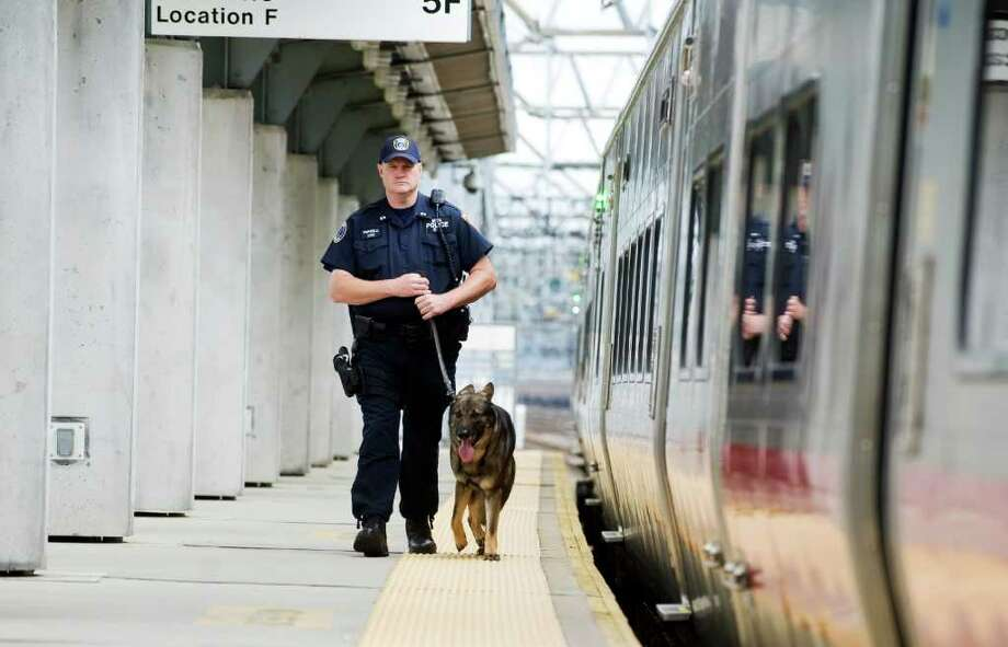 "MTA Police Officer Kevin Pimpinelli walks along the tracks at the Stamford train station with his K-9 unit dog ""Mullen"" in Stamford, Conn. on Tuesday June 14, 2011. Mullen recently won top dog honors in the U.S. Police Canine Association's annual finals. Photo: Kathleen O'Rourke / Stamford Advocate"