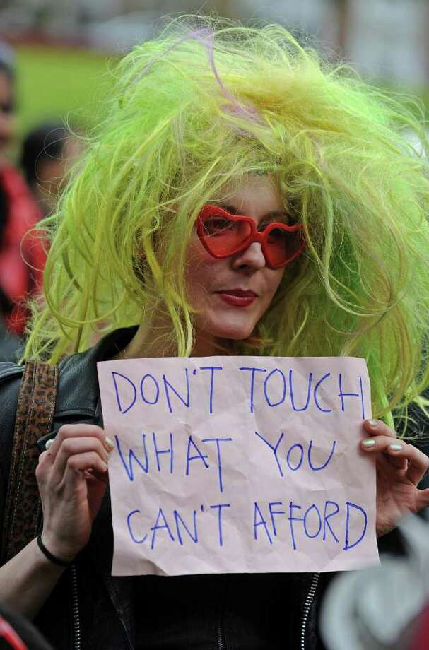 """A participant holds a sign during a rally following a march for """"SlutWalk"""" through Sydney on June 13, protesting for women to be able to wear whatever they like without fear of being sexually assaulted. A SlutWalk will take place in Seattle on Sunday from Capitol Hill to downtown.     AFP PHOTO / Greg WOOD Photo: GREG WOOD, AFP/Getty Images / 2011 AFP"""
