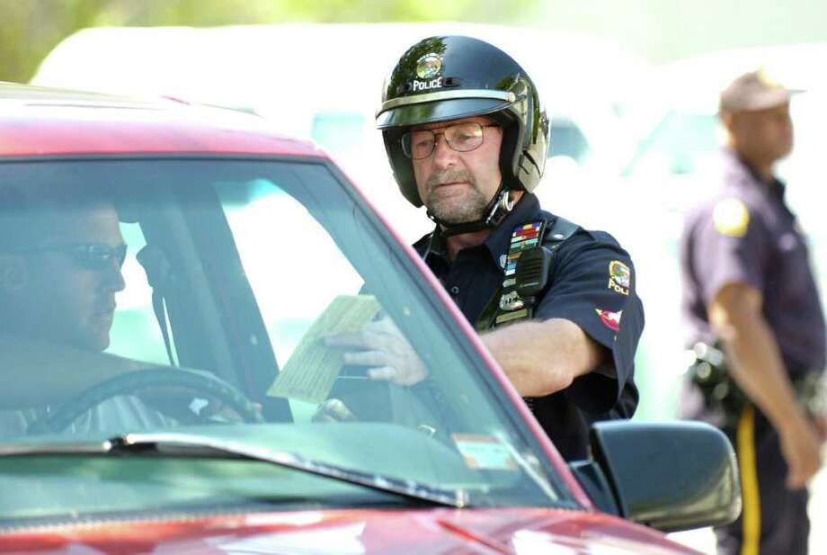 """Greenwich Police Officer Ron Carosella checks the registration on a vehicle just before giving a $37 dollar ticket to an unidentified motorist for not wearing a seat belt during """"Click It or Ticket"""" police checkpoint on Delavan Avenue in Byram, in this May 2007 file photo. Photo: File Photo / Greenwich Time File Photo"""