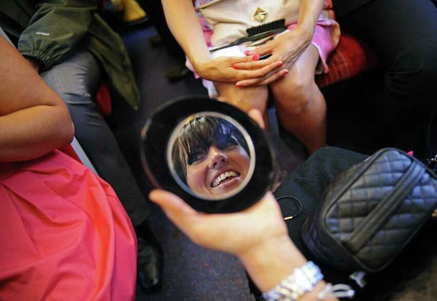 A race-goer is reflected in her make up mirror as she does her make up on a train on Ladies Day at the annual Royal Ascot horse racing event near Windsor, Berkshire.