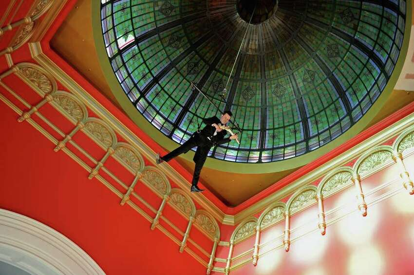Australian classical musician Shenzo Gregorio plays an electric violin while suspended under the dome of the historic Queen Victoria Building in Sydney, Australia.